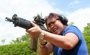 Kim Henares, head of the Philippines' Bureau of Internal Revenue, fires an automatic rifle during target shooting practice. Photo: Bloomberg, as posted in www.scmp.com